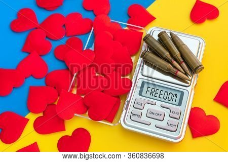 Gun Cartridges And Red Hearts On Scales On Blue Yellow Background Close Up. War And Peace, Love And