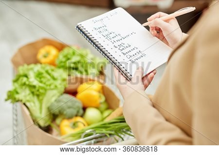 Close Up Of Unrecognizable Young Woman Holding Shopping List While Buying Groceries At Farmers Marke
