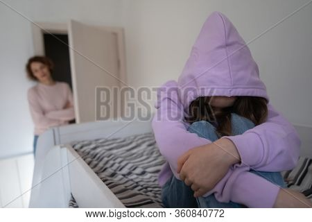 Depressed Teen Girl Wearing Hood Sitting On Bed Ignoring Mother