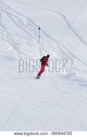 Snowboarder In Red Descends On Snowy Ski Slope After Snowfall At Gray Winter Day