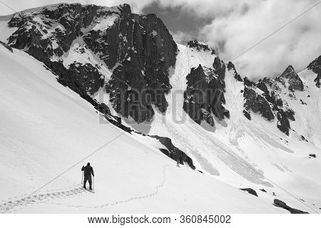 Snowy Mountains With Avalanche Traces, Sunlit Cloudy Sky, Hiker With Ski Poles And Dog On Snowy Slop