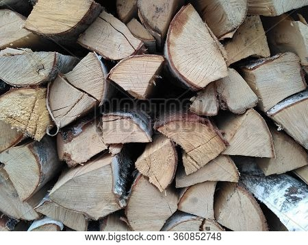 Chipped Firewood Is On The Heap. Woodpile Of Firewood Close-up. A Stack Of Dry Firewood, Visible Tex