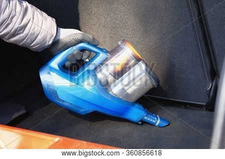 Vacuum Cleaner In Hands Of Driver. Cleaning Of Trunk Of The Car With Blue Vacuum Cleaner. Car Is Reg