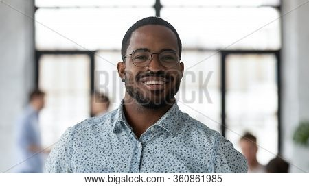 Headshot Portrait Of African American Businessman Posing In Office