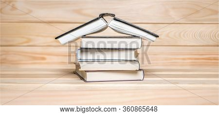 Banner Of Stay At Home Concept. House Made With Books Piled On Wooden Background. Stack Of Books. Ed