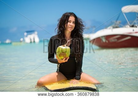 Portrait Of A Beautiful Surfing Girl With Green Coconut From Palm Tree Sit On Yellow Surf Longboard