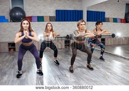 Group Of Four Young Fit Girls Doing Squats In Fitness Class. Sport, Fitness And Lifestyle Concept.