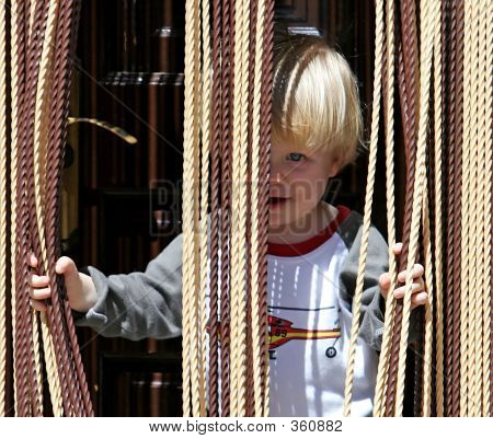 Young Boy Looking Out From Behind Curtain