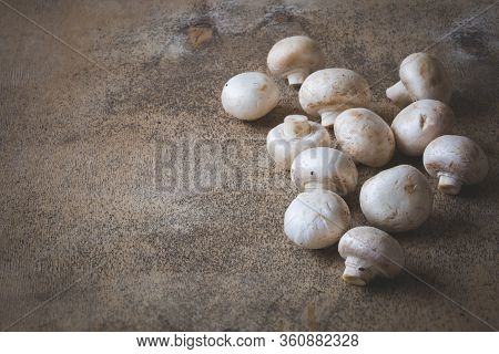 Many Champignons Lies On An Old Wooden Table. Freshly Cut Organic Champignons. Healthy Eating Concep