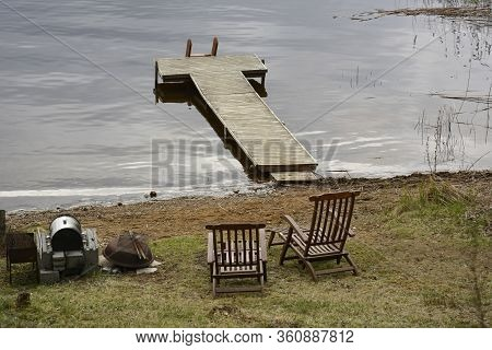 Southern Karelia, Finland, May, 10, 2014. Lake Waterside With Dock. Green Grass On The Shore. Two Wo