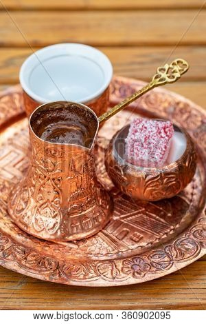 Traditional black bosnian coffee in beautiful copper cezve at wooden table. A complete Bosnian coffee set is called a kahveni takum