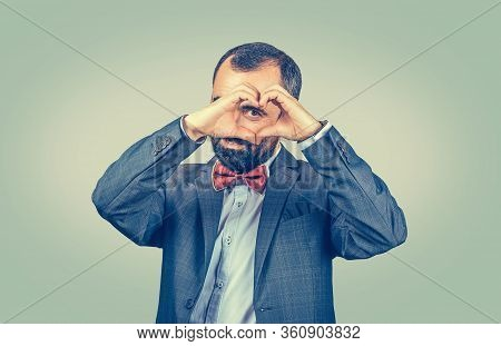 Handsome Smiling Young Man Makes Heart Shape With Fingers, Hands, Isolated On Light Green Wall Backg
