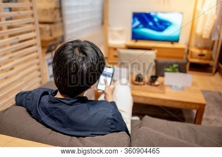Young Asian Man In Casual Clothing Sitting On Comfortable Sofa (couch) Using Smartphone And Watching