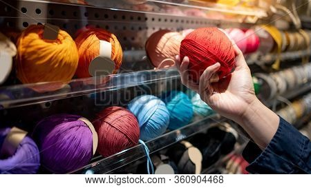 Male Hand Choosing Red Yarn Ball In Knitting Shop Or Needlework Shop. Selection Of Colorful Yarn Woo