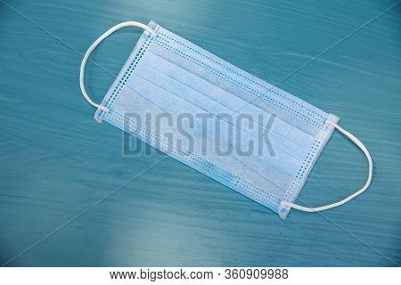 Blue Surgical Mask On  Blue Background.