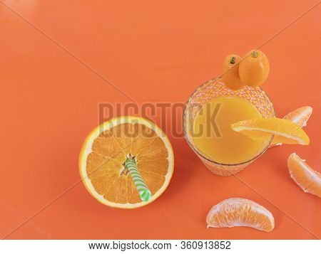 Orange Juice, Small Oranges And Sliced Oranges On An Orange Background - Nutritious And Tasty Orange