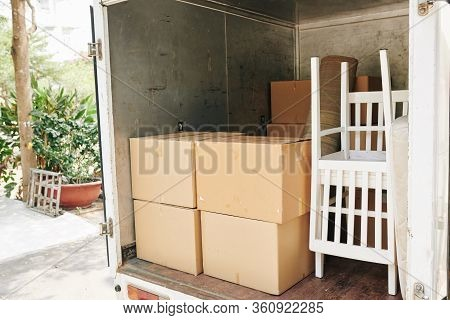 Truck Loaded With Furniture And Cardboard Boxes Of Family Moving Out From The House