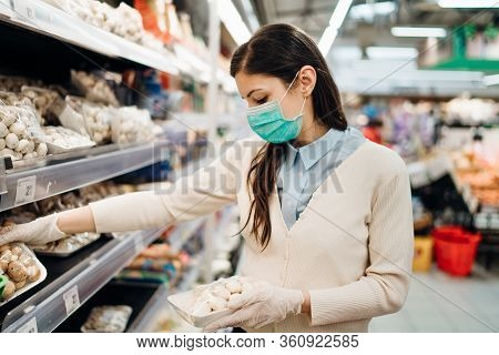 Woman With Mask Safely Shopping For Groceries Amid The Coronavirus Pandemic In A Stocked Grocery Sto