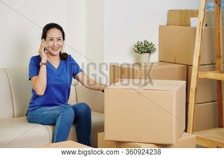 Smiling Mature Asian Woman Calling To Moving Service Company After Packing Her Belongings In Cardboa