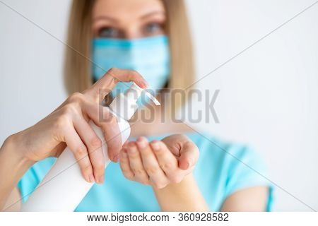 Female Doctor Or Nurse In Uniform Puts A Disinfectant Soap On Her Hands. Disinfection And Hand Washi