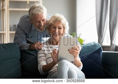 Happy Older Couple Using Computer Tablet Together At Home