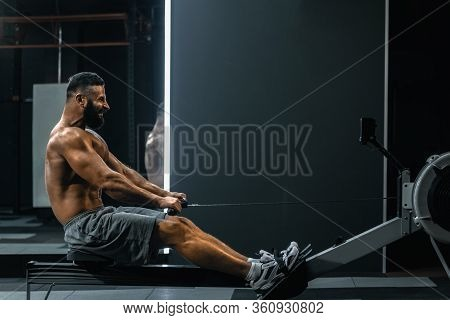 Side View Of Strong Healthy Man Doing Exercises With Rowing Machine In Modern Gym