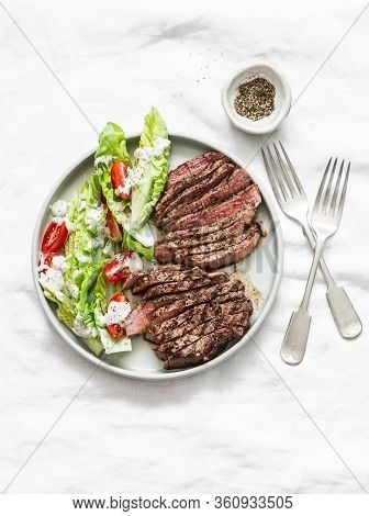Beef Steak And Romaine Cherry Tomatoes Yogurt Dressing Salad On A Light Background, Top View