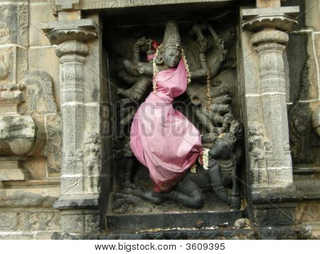 This once-perfect statue of the Hindu goddess Kali/Durga is shown killing a horse-demon. It stands in one of the holiest temples of India the Sabhanayaka Nataraja temple in Chidambaram Tamil Nadu. It is about 1000 years old and during this time one of the poster