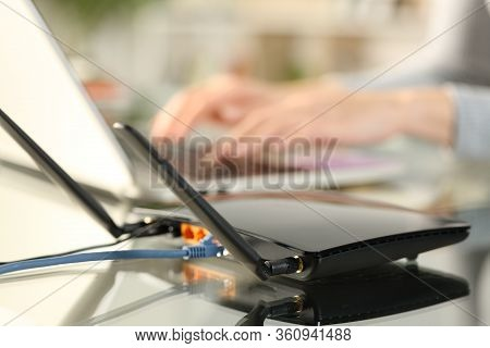 Close Up Of Broadband Router Wifi Providing Connection To Woman Hands Using Laptop On A Desk At Home
