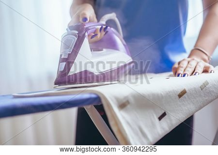 The Girl Irons The Iron Of Things On The Ironing Board With The Ferry. Cleaning Of The Apartment. Bl