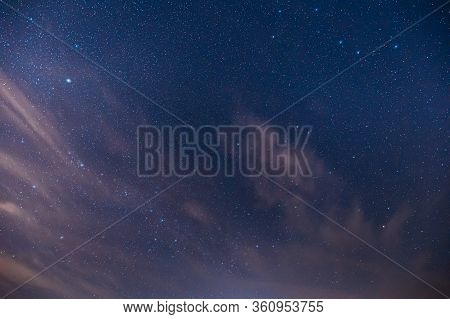 Real Night Sky Stars. Colorful Starry Sky With Some Clouds Background Backdrop.