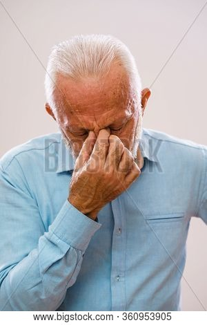 Portrait Of Senior Man Who Is Having Pain In Sinus.