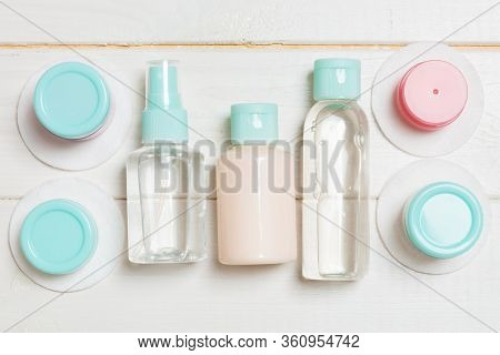 Set Of Travel Size Cosmetic Bottles On White Wooden Background. Flat Lay Of Cream Jars. Top View Of