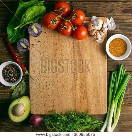 Wooden Board With Clear Space. Around Tomato And Dill, Olive Oil, Peper, Avocado, Green Onion, Spina