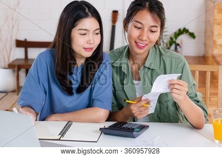 Asian Lesbain Couple Together Calculate Home Budget With Paper Bill In New House At Table In Kitchen