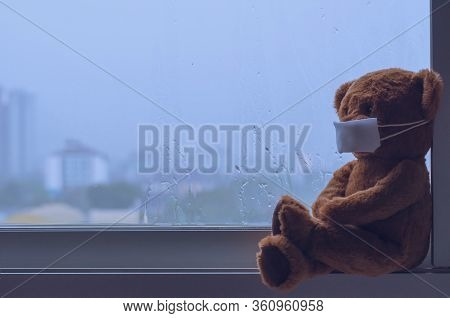 Teddy Bear Wearing Mask Sitting At Window While Raining In Monsoon Season. Stay Home Away From Virus