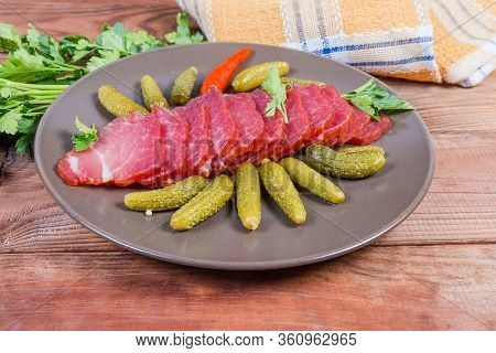 Sliced Air-cured And Smoked Pork Neck With Pickled Gherkins On The Brown Dish On The Rustic Table Wi