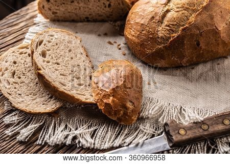 Three Slices Of Fresh Crusty Bread On A Rustic Cloth And Wooden Background With A Knife On The Side