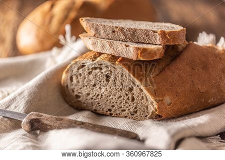 Two Slices Of Freshly Baked Bread Placed On Top Of The Loaf And A Linen Cloth With A Knife On A Side