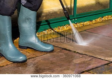 Person Using A Pressure Washer To Clean A Patio Area In A Garden
