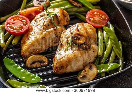 Close-up Of Healthy Home Cooked Food, Grilled Chicken In A Skillet With Green Vegetable, Mushrooms A