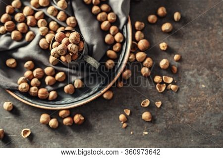 Top View Of Hazelnuts And Their Cracked Shells On A Rustic Dark Metallic Background, In A Metallic C
