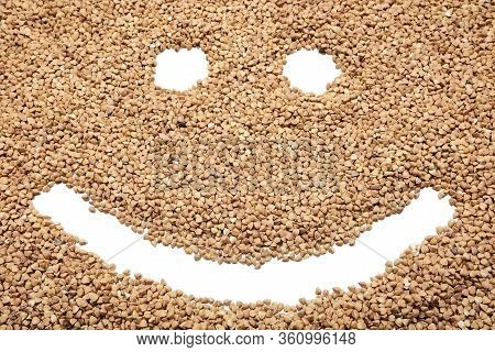 A Smiling Face On Buckwheat. Raw Buckwheat With A Smiling Emoji Face