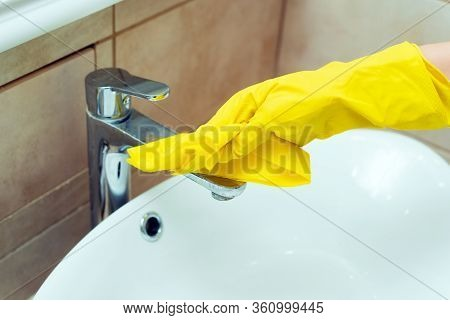 Someone Is Washing A Sink In Yellow Gloves. Someone Is Cleaning A Bathroom With Detergents.