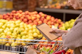 Mature female consumer with notepad over food products in cart looking through shopping list while moving along fruit display