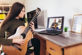 Focused Girl Playing Acoustic Guitar And Watching Online Course On Laptop While Practicing At Home.