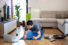 Young Man Exercising Doing Workout At Home In Front Of Laptop