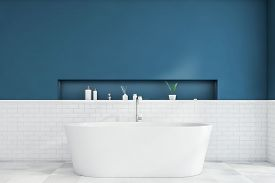 Interior Of Modern Bathroom With Blue And White Brick Walls, Tiled Floor, Comfortable White Bathtub