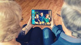 Senior Couple Video Chatting On Digital Tablet With Son And Grandchildren Due To Home Isolation Quar