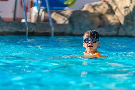 A Happy Boy In Swimming Goggles And Arm Ruffles In An Outdoor Pool. The Child Learns To Swim. Family
